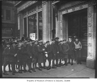 Boys waiting outside Washington Mutual Savings Bank for Boy Scout party, Seattle, ca. 1920