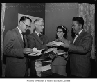 Joel Pritchard, Gordon Hannaford, C.G. Witherbee and wife Esther with a pile of books, possibly in...