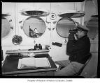 U.S. Coast Guard home defense patrol crew member inside the ship and looking though a porthole,...
