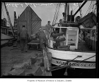 Halibut fishermen load boat 'Kodiak' with supplies, Fishermen's Terminal, Seattle, July 1, 1947