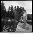 Opening day of trout fishing season showing a man and a boy fishing from a dock, probably in...