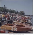 Motorboats and youth in racing gear on the shore of Green Lake, Seattle, 1953