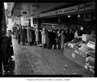 Shoppers lined up in front of E&E Meat Market on Olive Way for meat during wartime rationing,...