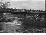 Motorboat race at Sammamish Slough showing a boat passing under a bridge, Redmond, April 1961