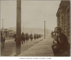 Boy watching cavalry ride past Second and Pine, Seattle, August 7, 1900