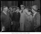 Jack Dempsey in military uniform and standing with workers at Todd Shipyards, Seattle, 1944