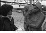 Woman looking at 'Waiting for the Interurban' sculpture, Seattle, March 1987