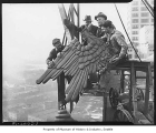 Workmen putting eagle ornament on County-City Building, Seattle, 1937
