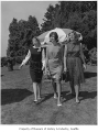 Antoinette Paschall, Melinda Berge, and Virginia Isaacson, debutantes walking on a lawn probably...