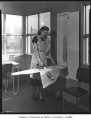Woman ironing on built-in ironing board, probably in Seattle, 1948
