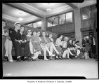 Greyhound Bus Terminal waiting room showing people on bench, Seattle, 1948