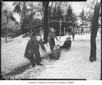 Women pulling children on sleds in Volunteer Park, Seattle, November 19, 1946