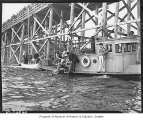 Diver with harbor patrol boat searching for body beneath East Channel Bridge, Mercer Island, 1937