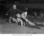 University of Washington wrestling coach James Arbuthnot with two wrestlers , Seattle, ca. 1925