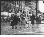 Christmas shoppers crossing street in rain, Seattle, 1939