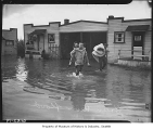 People leaving flooded house during Green River flood, Kent, 1938