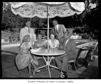 Scripps and Freeman husbands and wives at a table near a pool, possibly in Bellevue, 1960