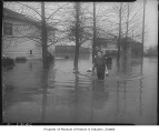 Carl Elliott carrying Carola Elliott through floodwater, Earlington, 1947