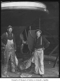 Two men in front of ship hull holding flag, probably in Seattle, ca. 1910