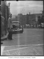 Woman in work clothes waiting to cross street, Seattle, 1942
