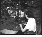 Woman sewing in garment factory, Seattle, 1954