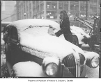 Kathy Gustafson clearing snow from windshield, Seattle, 1947