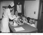 Nurse examining children at Bryant School, Seattle, 1945
