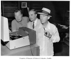 Bing Crosby with Phil Harris and Bob Littler listening to record player, Seattle, 1956