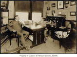 Morgan and Vivian Carkeek seated in office, circa 1920s