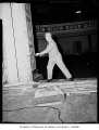 Metropolitan Theatre interior during demolition showing a man in a suit with a sledgehammer and...