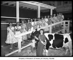 Washington State Dairy Princesses at the University Plaza cow barn, Seattle, 1958