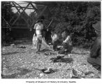 Chris Larsen and Gilbert Hayes making flapjacks with Gladys Meyers in costume, Duvall, 1947