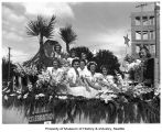 Miss Enumclaw rides a float with pageant princesses for Enumclaw's Golden Jubilee Parade, 1939