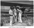 Biplane pilots secure their protective masks before crop dusting, Yakima Valley, 1944