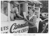 Man selling popcorn from concession truck, Seattle, June 1938