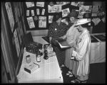 Three women looking at advertising materials at the American Home Economics Association meeting,...
