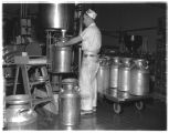 Darigold worker filling metal canisters with milk, Issaquah, 1961