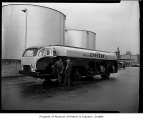 Chevron gasoline tanker truck parked near large tanks, probably in Seattle, 1959