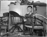 Goodwill employee repairing a chair, 1948