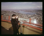 Man holding a boy looking though a telescope on the Space Needle observation deck, May 22, 1963