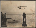Seaplane flying over water with spectators on shore, Golden Potlatch, Seattle, ca. 1913