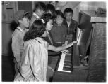 Teenage internees gather at a piano, Camp Harmony, Puyallup, 1942