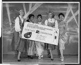Women in traditional costume posing with a giant admission ticket to the Century 21 Exposition,...