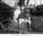 Dog musher Leonhard Seppala with famous sled dogs Togo and Fritz aboard steamship, Seattle, 1926