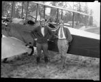 Miss Seattle poses with biplane and pilot at Sand Point, 1926