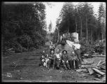 Children and logging crew with a big log, ca. 1903