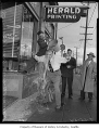 Man getting water poured over his head outside the West Seattle Herald office, Seattle, 1954