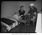 Civil Defense officer with a woman and a child inside a house, possibly in Seattle, 1943