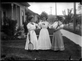 Three women in front yard with tennis rackets, ca. 1900