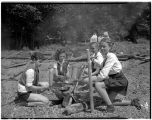 Camp Fire Girls cooking food over a fire, August 7, 1937